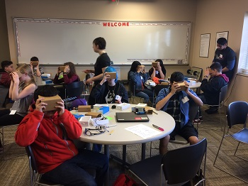 Students try on some cardboard VR goggles.