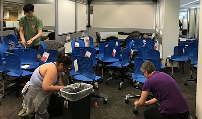 Library employees assemble some chairs.